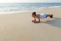Plankenübung auf dem Strand Lizenzfreies Stockfoto