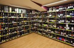 Planken met flessen Het opschorten, winkel Stock Foto's