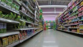 Planken met goederen in supermarkt Kruidenierswinkel die van mening van een boodschappenwagentje winkelen thailand stock videobeelden