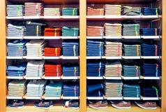 Planken met T-shirts en tennisschoenen in een grote kledingsopslag stock foto