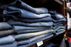Planken van gevouwen en goed voorgestelde jeans stock afbeeldingen