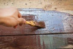 Plankenomheining die met bruine verf en borstel verven Stock Foto