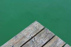 Plankenrand über grünem Wasser Stockbild