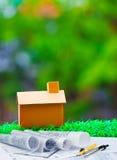 Plankompas en administratie met huis op groen gras met onduidelijk beeld B Stock Fotografie