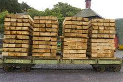 Plankor av trä som staplas på vagnen. Arkivfoto
