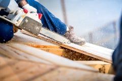 Plankor för arbetarklipptimmer genom att använda den elektriska sågen detaljer av konstruktionsplatsen Arkivbilder