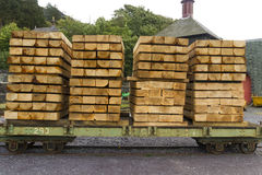 Planks of wood stacked on wagon. Edge on planks of wood stacked high on narrow gauge railway carriages Stock Photo