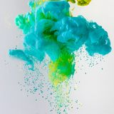 planlägg med flödande turkos, slösa och göra grön målarfärg i vatten med droppar som isoleras på grå färger royaltyfri foto