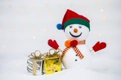 Planlägg snögubben med den skinande gåvaasken och sörja kotten på vit snö arkivbilder