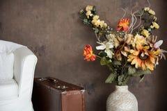 Planlägg tappninginre med blommor i resväskor och cha för en vas Fotografering för Bildbyråer