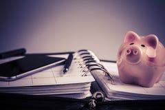 Planläggningsbegrepp - kalender, mobiltelefon, penna, svinmoneybox Arkivbild