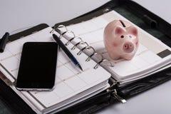 Planläggningsbegrepp - kalender, mobiltelefon, penna, svinmoneybox Arkivbilder