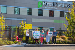 Planned Parenthood Eugene Oregon. EUGENE, OR - OCTOBER 4, 2015: Anti-abortion protesters target pedestrian and vehicle passersby in front of Planned Parenthood Stock Photo