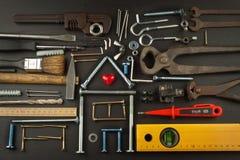 Plannen om een huis te bouwen Rustieke houten achtergrond Hulpmiddelen voor bouwers Architect die een huis voor een jonge familie Stock Fotografie