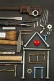 Plannen om een huis te bouwen Rustieke houten achtergrond Hulpmiddelen voor bouwers Architect die een huis voor een jonge familie Stock Foto