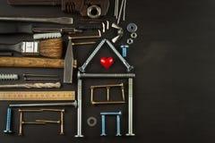 Plannen om een huis te bouwen Rustieke houten achtergrond Hulpmiddelen voor bouwers Architect die een huis voor een jonge familie Royalty-vrije Stock Foto's