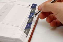 Planner. Hand holding a pen and a planner Royalty Free Stock Photo