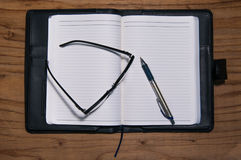 Daily planner book in black leather case with glasses and pen Stock Photos