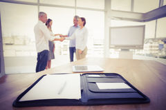 Planner in front of handshaking business people Stock Photos
