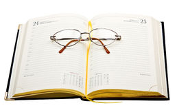 Daily planner with glasses isolated on white. Background Royalty Free Stock Photography