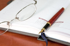 Daily planner with glasses and pen Stock Images