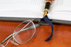 Daily planner with glasses and pen Royalty Free Stock Image