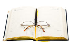 Daily planner with glasses and pen Royalty Free Stock Photography