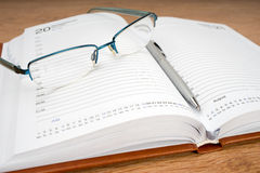 Daily planner. With glasses and pen on the table Stock Images