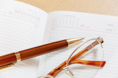 Daily planner with glasses and pen on the table Stock Images