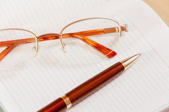 Daily planner, glasses and pen on the table. Selective focus Royalty Free Stock Photo
