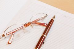 Daily planner with glasses and pen on the table. Selective focus Stock Photo
