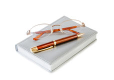 Daily planner with glasses and pen on white background Stock Image