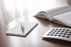 Planner with  pen and calculator. On the table Stock Image