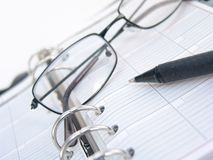 Planner, pen and glasses royalty free stock photography
