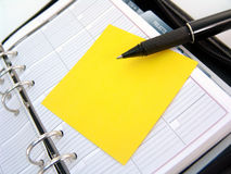 Planner, sticky note and pen. Ringed planner with yellow sticky note and pen royalty free stock photos
