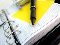 Planner, sticky note and pen. Ringed planner with yellow sticky note and pen Royalty Free Stock Photo