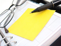 Planner, sticky note, pen and glasses Royalty Free Stock Images