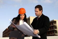 Planning. Two architects standing in front of a building site checking project Stock Photo