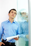 Planning. Portrait of pensive man with documant looking upwards in office Stock Photos