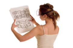 PLanning. Young girl watching at arch planning of her house through protect worker eyeglasses Royalty Free Stock Photography