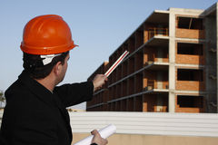 Planning. Architect wearing a protective helmet pointing to building Royalty Free Stock Photos