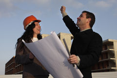 Planning. Two architects standing in front of a building site and signing success Royalty Free Stock Photo