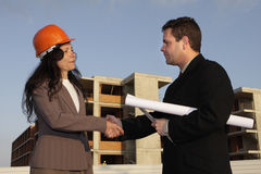 Planning. Two architects standing in front of a building site and shaking hands Royalty Free Stock Photography