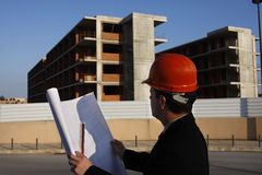 Planning. Architect wearing a protective helmet standing in front of a building site Royalty Free Stock Image