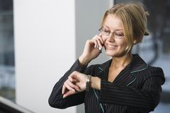 Planning of the business meeti. Beautiful blond young woman in black suit is speaking on her cell phone and noting the time Stock Image