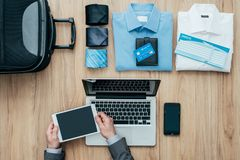 Planning a business travel. Planning a business trip: corporate businessman packing his bag and using a digital touch screen tablet, travel and communication Royalty Free Stock Photography