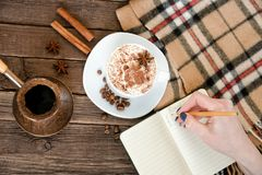Planning in a cafe. Mug latte, a female hand writing in a notebook with a pencil. Top view Stock Images
