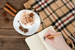 Planning in a cafe. Mug latte, a female hand writing in a notebook with a pencil. Top view Royalty Free Stock Photo