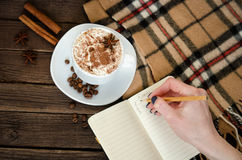 Planning in a cafe. Mug latte, a female hand writing in a notebook with a pencil. Royalty Free Stock Photo