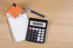 Planning and costing home improvements concept. With a calculator, pen and notebook with a small model of a house on a wooden desk royalty free stock images